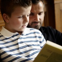 Father and son reading a book together.